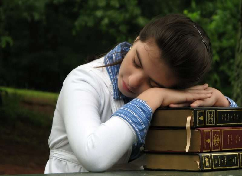 Student sleeping over a stack of books