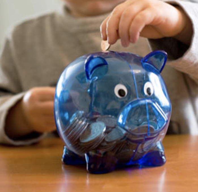 Young boy putting coin into a piggy bank